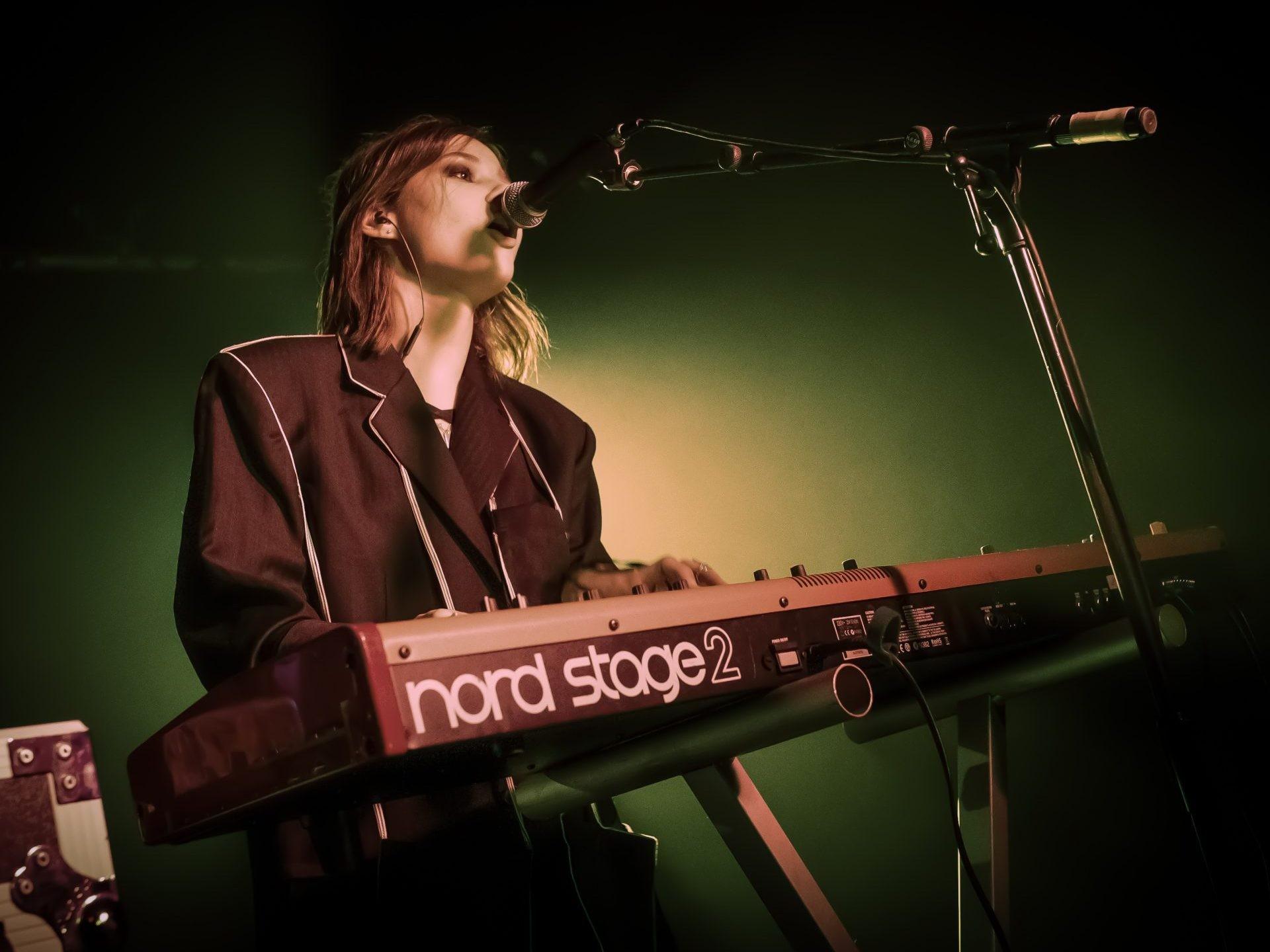 person singing playing keyboard